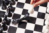 Hand with white pawn hits black king — Stock Photo