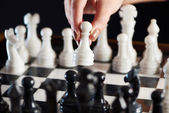 Hand with white pawn over chessboard — Stock Photo
