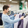 Man chooses shirt in store — Stock Photo #69132527
