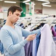 Surprised man looking at price tag of goods — Stock Photo #69132669
