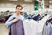 Hombre elige la camisa en la tienda — Foto de Stock