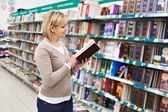Woman chooses book in store — Stock Photo
