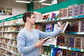Man chooses book in store — Stock Photo