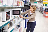 Woman housewife shopping for microwave oven — Stock Photo