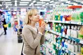 Woman smelling fragrant liquid soap in store — Stock Photo
