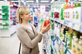 Woman chooses fragrant liquid soap in store — Stock Photo