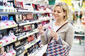 Woman chooses pink liquid lipstick — Stock Photo