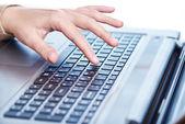Female hand on laptop keyboard — Stock Photo