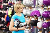 Girl chooses helmet for roller skating — Foto de Stock