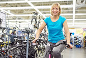 Attractive athletic woman testing bike in store — Photo