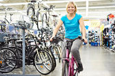 Attractive athletic woman testing bike in store — Stockfoto