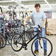Man checks bicycle before buying in sports shop — Stock Photo #70209139