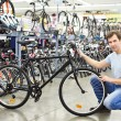 Man checks bicycle before buying in sport shop — Stock Photo #70209211