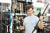 Man chooses fishing rod in sports shop — Stock Photo