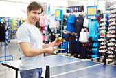 Man chooses table tennis racquet in shop — Stock Photo