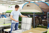 Man chooses folding camp table in store leisure goods — Stock Photo