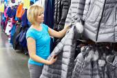Woman shopping for winter jacket in shop — Stock Photo