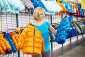 Happy woman shopping for baby jacket in shop — Stock fotografie