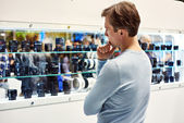 Selecting camera lens in showcase of store — Stock Photo