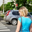 Young woman stands at traffic light and waiting for green signal — Stock Photo #75637379