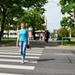 Woman crossing street is dangerous at red light — Stock Photo #75637835