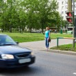 Young woman stands at traffic light and waiting for green signal — Stock Photo #75639213