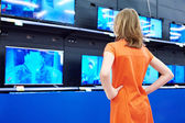 Teenager girl looks at LCD TVs in shop — Stock Photo