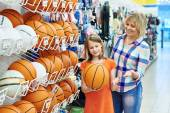 Mother and daughter shopping basketball ball — Stock Photo