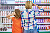 Mother and daughter choosing dairy products — Stock Photo
