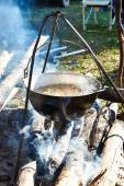 Cooking soup in hiking bowler over a campfire — Stock Photo