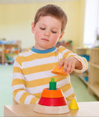 Boy collects colored pyramid — Stock Photo