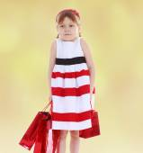 Little girl goes shopping with red packets. — Stock Photo