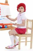 Girl in a red beret sits at an easel — Stock Photo