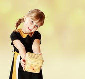 Girl holding at arms length wicker basket. — Stock Photo