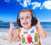 Little girl listening to music on headphones. — Stock Photo