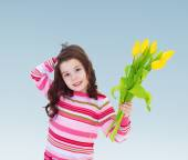 Adorable little girl holding a bouquet of yellow tulips. — Stock Photo