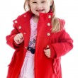 Fashionable little girl bright red coat in a beautiful pink dress. — Stock Photo #55479545