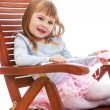 Cheerful little girl is resting on a large wooden chair. — Stock Photo #55480089