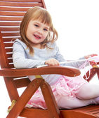 Cheerful little girl is resting on a large wooden chair. — Stok fotoğraf