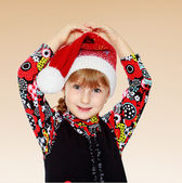 Little girl in santa claus hat ale a lesson. — Stock Photo
