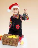 Little girl in santa claus hat holding a bunch of grapes. — Stock Photo
