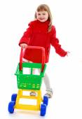 Cheerful little girl in red coat utilities products. — Stock Photo