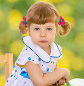 Little girl sitting at a desk and looking into the camera. — Stock Photo