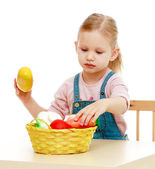 Little girl lying disassembled in a fruit basket. — Stock Photo