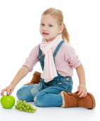 Little girl sitting on the floor and holding a hand an apple. — Stock Photo