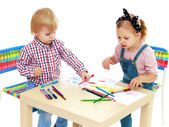 Girl and boy sitting at the table draw. — Stockfoto