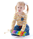 Little girl holding a childrens musical instrument. — Stock Photo