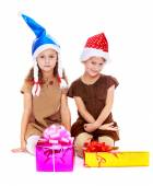 Two cute sisters in Christmas hats are considering gifts. — ストック写真