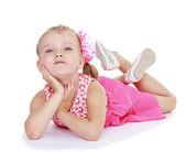 Adorable little girl lying on the floor. — Stock Photo
