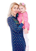 Adorable little daughter sits on hands at mum. — Stock Photo